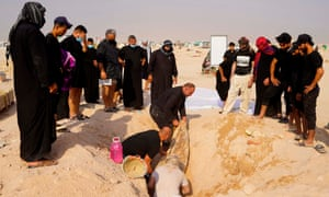 An Iraqi family searches for the body of a relative in a Coronavirus cemetery outside the holy Shiite city of Najaf.