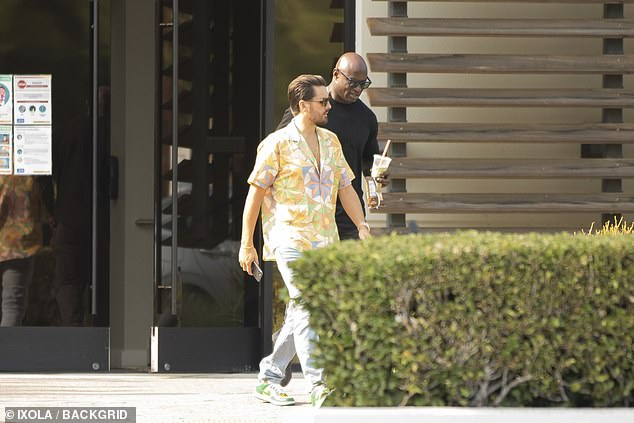 Scott's Look: Disick is seen wearing a multi-colored, partially buttoned top and light blue jeans