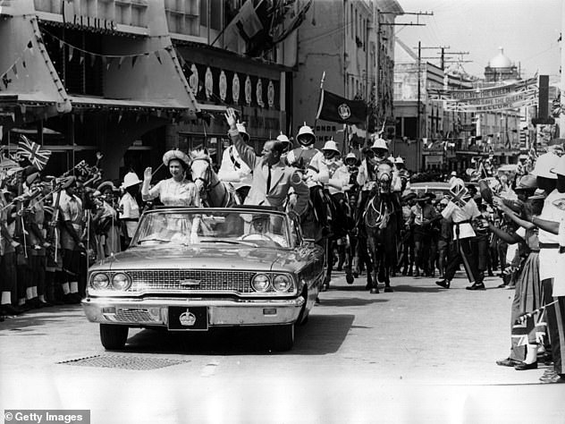 Memories: The Queen and Prince Philip are photographed driving through Barbados waving to crowds in February 1966