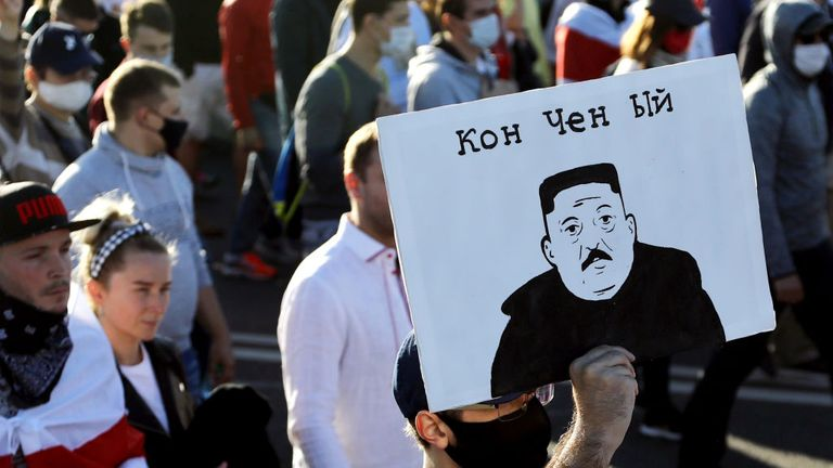 """Man holding a banner with a picture of Belarus'  The president like North Korean leader Kim Jong Un and reading """"Washed away by the waves"""" During a demonstration called by the Opposition Movement for an End to the Autocratic Leader's Regime in Minsk on September 20, 2020 - Belarusian President Alexander Lukashenko, who ruled the former Soviet state for 26 years, claimed that he defeated opposition leader Svetlana Tikhanovskaya with 80 percent of the vote in the August 9 elections.  (Photo - / TUT.BY / AFP) (Photo - / TUT"""