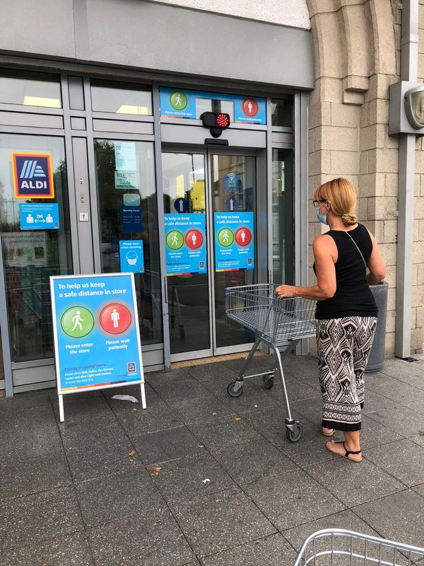 A customer waits outside the Aldi store in Plymouth where the traffic light entry system is installed