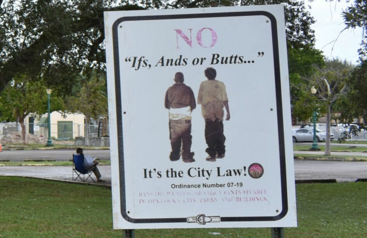 Signs in a park warn passersby about the saggy pants law