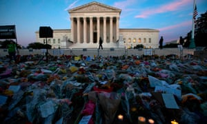 Flowers, candles, and banners depicted in a monument outside the Supreme Court.