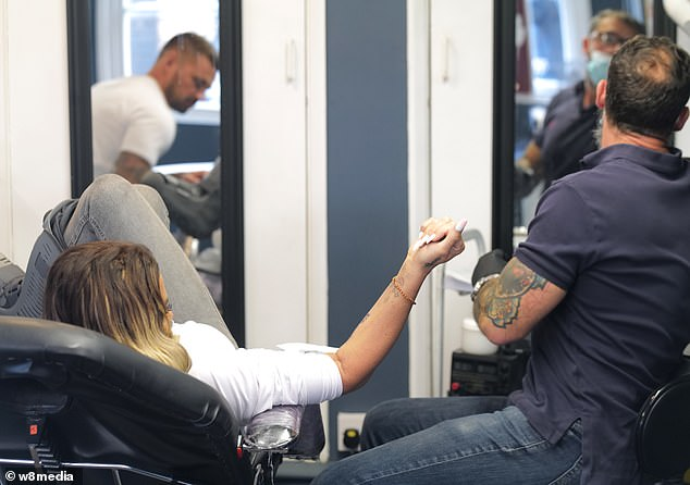 Complicated: The tattoo artist looked with deep focus while working on Katie's arm tattoo last month