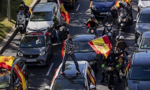 People wave Spanish flags during a protest organized by the far-right Vox party in Spain.