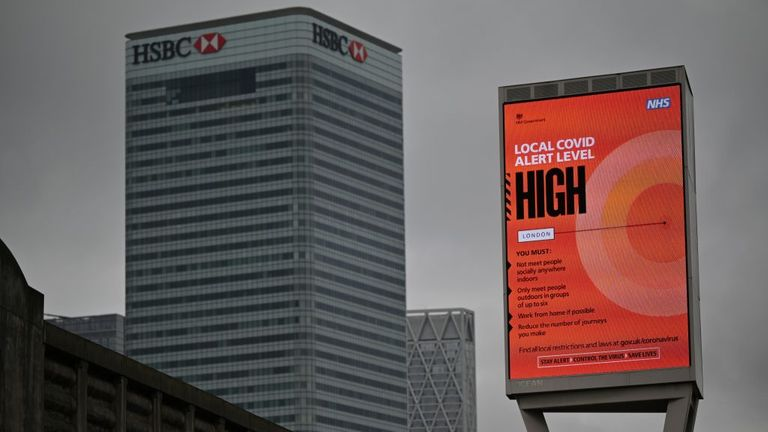 """Flag that displays your local Covid alert level as """"high"""" Pictures were taken near Canary Wharf in East London, on October 17, 2020, as Londoners face tougher restrictions on the novel coronavirus COVID-19 as the number of cases rises.  The government announced that London had moved to the second level, the High Alert level, from three levels of restrictions.  (Photo by Justin Thales / AFP) (Photo by Justin Thales / AFP via Getty Images)"""