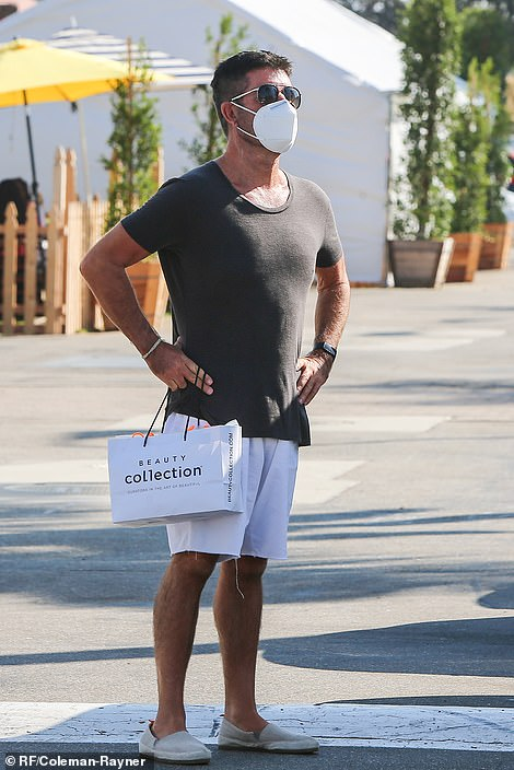 Family man: Simon Cowell has been seen in public for the first time since he broke his back, 10 weeks ago, when he went out with his partner and son