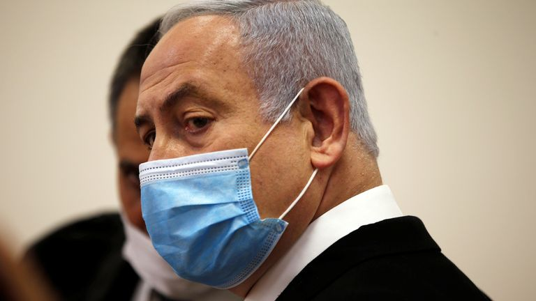 Israeli Prime Minister Benjamin Netanyahu, wearing a face mask, looks at him standing in the courtroom as his corruption trial begins at the Jerusalem District Court