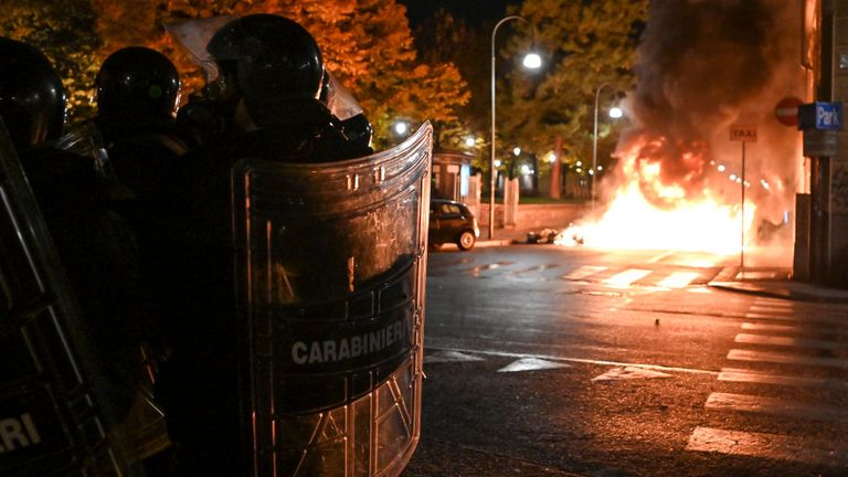 Police officers guard as protesters set fire to public property during an anti-government demonstration