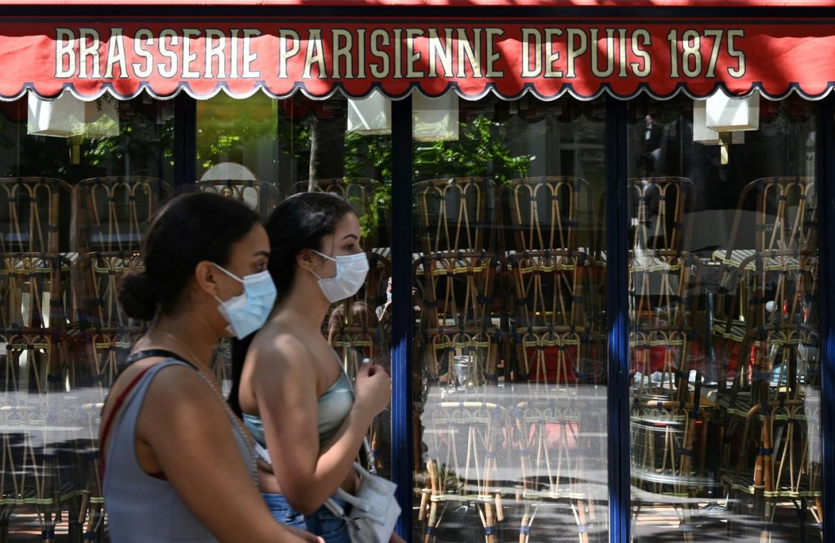 Women wearing a protective face mask pass in front a closed a restaurant in Paris on May 30, 2020, as France eases lockdown measures taken to curb the spread of the COVID-19 (the novel coronavirus)