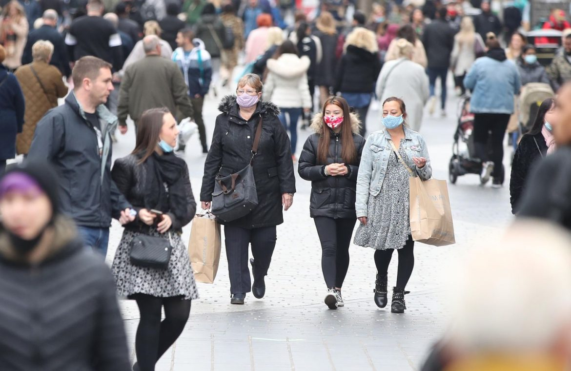 People wear masks in Liverpool city centre where new virus restrictions are in place