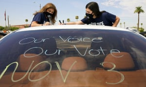 Patricia Santos, left, and her daughter Malia Santos mark their car before the cars congregate in August at the Arizona State Capitol in Phoenix.  A coalition of voting rights groups gathered in Arizona with the lofty goal of getting one million people to vote in November.