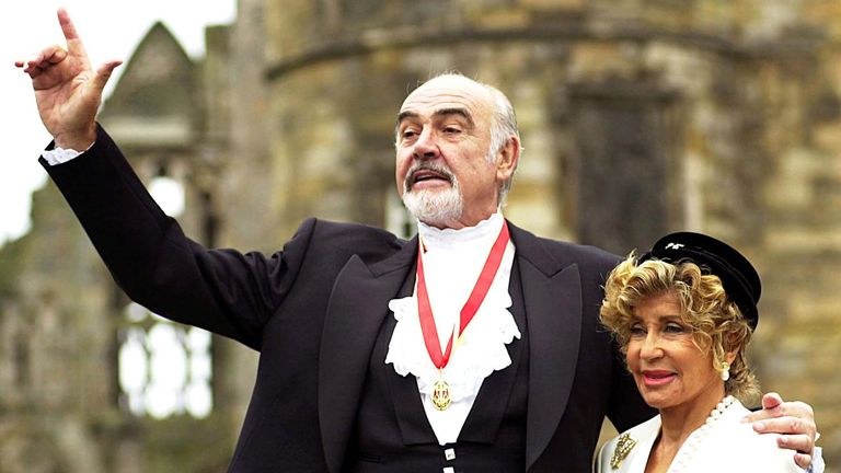 Sir Sean Connery, with his wife Michelin (right), pose in front of the paparazzi after he was officially awarded a knighthood .. Sir Sean Connery, with his wife Micheline (right), pose in front of the paparazzi after he was officially awarded a knighthood by Britain. [Queen Elizabeth] At Holyrood Palace in Edinburgh, July 5. [The Scottish screen legend, famous for his role as James Bond, was honoured two years after he was reportedly denied a knighthood because of his passionate Scottish nationalism. ]Upload image date: 07/05/2000 12:00 dime