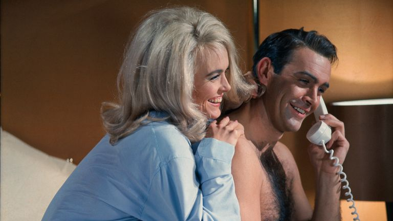Sean Connery and Jill Masterson (original caption) James Bond (Sean Connery) and Jill Masterson (Shirley Eaton) share laughs on the phone in the James Bond movie, Goldfinger. 1964.