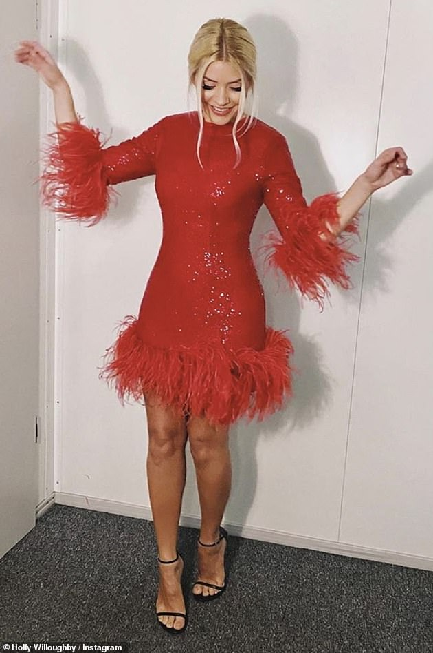 Festive feeling!  Feathers appear to be Holi's new favorite as she wears a sequin dress that features feather hem and cuffs while teasing her that she was `` photographing something festive. ''