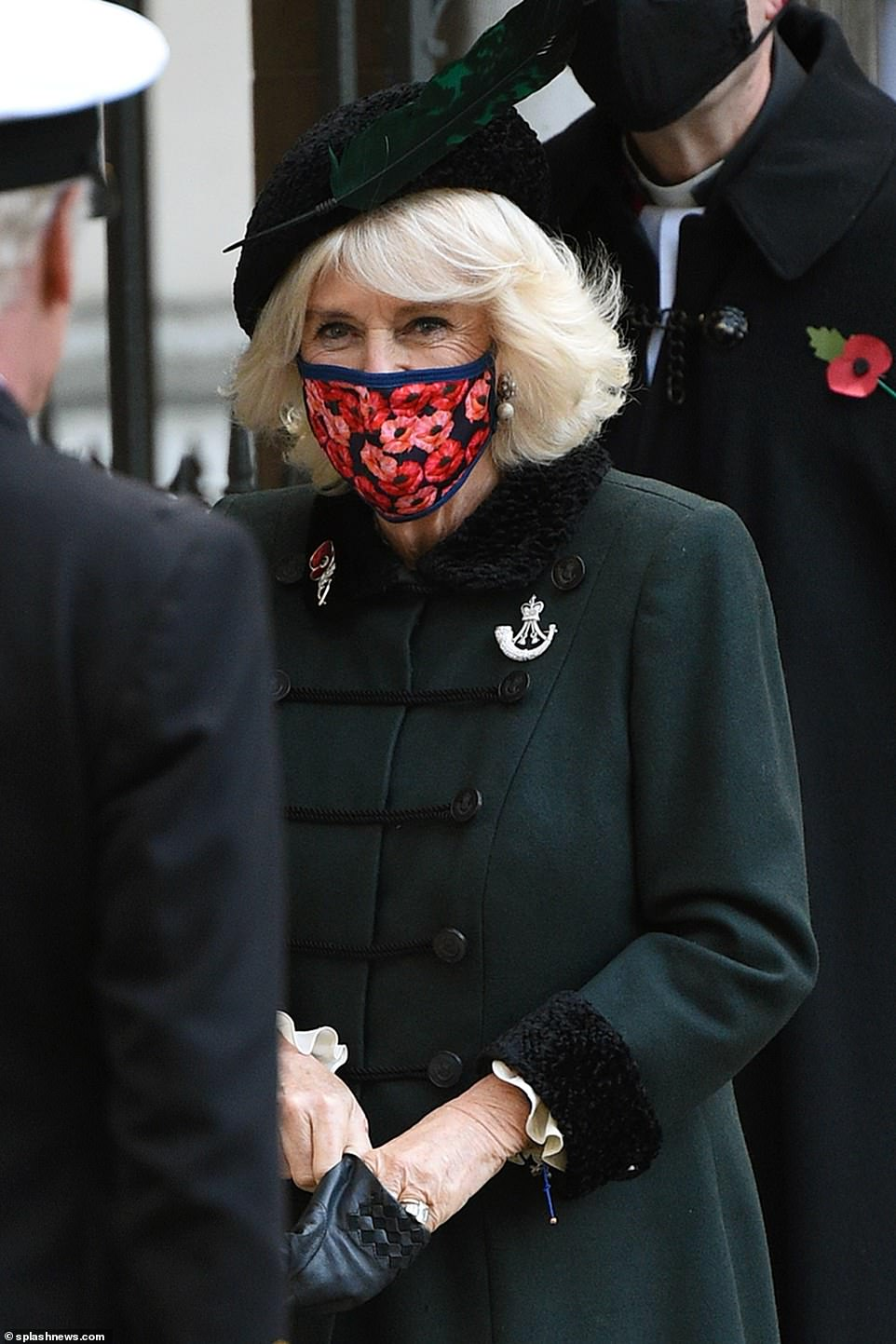 Camilla, 73, wearing a poppy face mask, pays homage to the soldiers and women who sacrificed their lives for their country and stood in solemn silence while the Last Post was played.