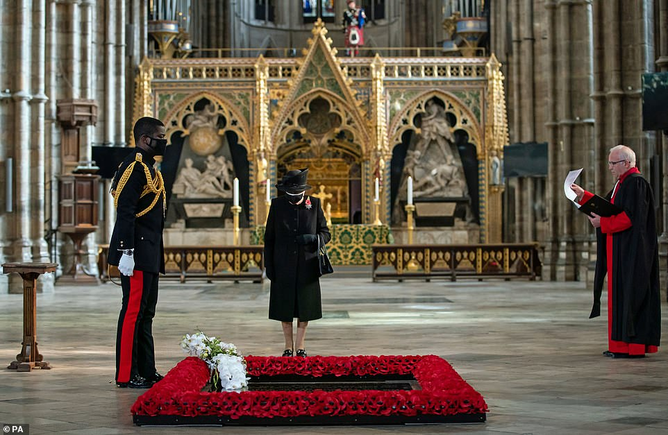 David Howell, Dean of Westminster Abbey (right), watches Queen Nana Kofi Tomasi-Ankara laying a bouquet of flowers on the grave of the unknown warrior in front of the Queen in Westminster Abbey.