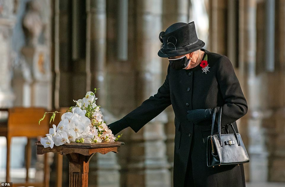 Commemoration: The Queen inspects a bouquet of flowers to put on the grave of unknown warrior Lieutenant Colonel Nana Kofi Tomasi-Ankara