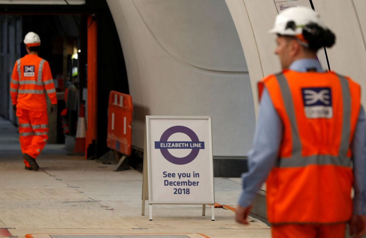 Crossrail employees walk in the new Farringdon underground station of the Elizabeth line which opens in December 2018