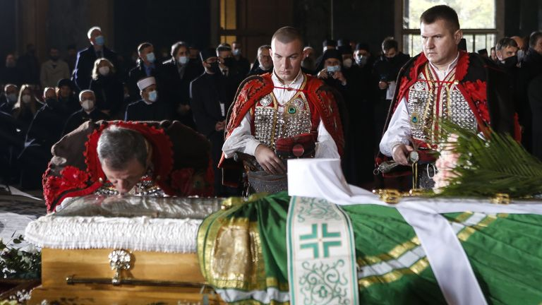 A man kisses Patriarch Ering's coffin during the funeral procession at the Temple of Saint Sava