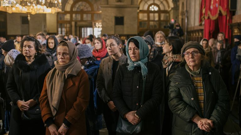 Orthodox believers attend the mass of the late Serbian Patriarch Ering during his funeral