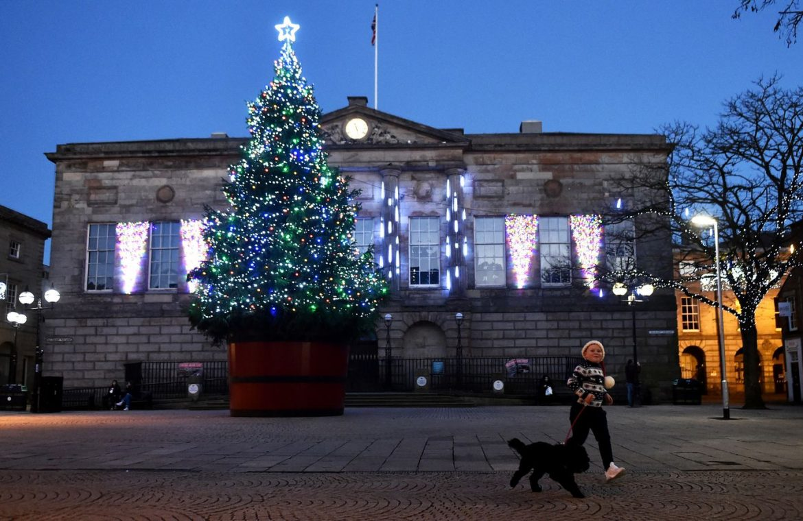 A boy and his dog runs past a Christmas tree at Stafford Town Hall on November 22, 2020 in Stafford, England