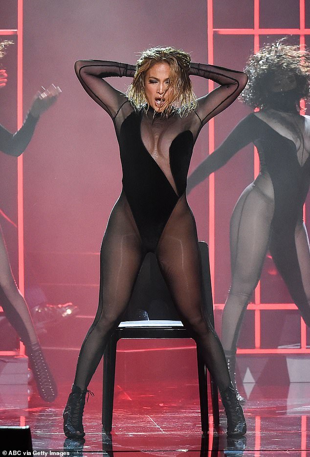 The action: Both women rocked heads full in short glossy locks, a translucent black jumpsuit, and danced on a chair