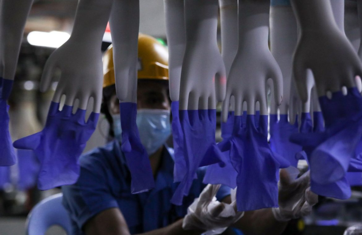 A worker inspects newly-made gloves at Top Glove factory in Shah Alam
