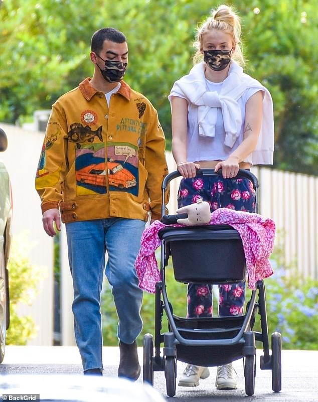 Take it easy: Joe Jonas and Sophie Turner are spotted taking their daughter Willa on a stroll near their Los Angeles home on Friday.