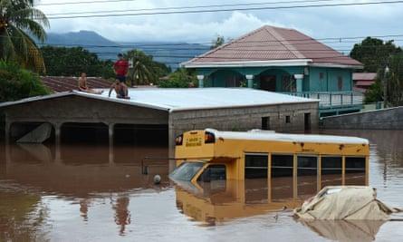 Men seek shelter on the roof of a house in Omonetta, Honduras