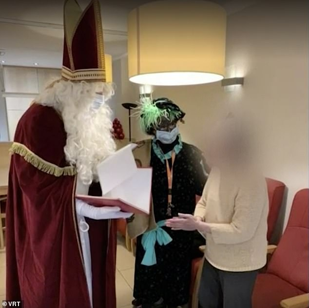 Father Christmas talking to an elderly resident.  It appears that he and his assistant are standing more than two meters away from her