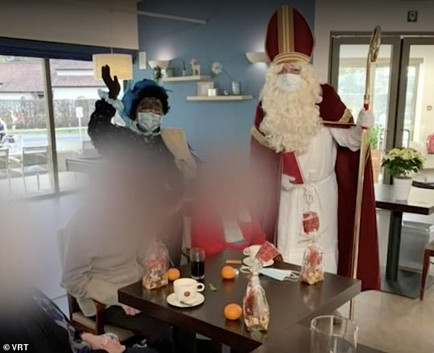 The volunteer dressed as Sinterklaas was welcomed to spread Christmas cheer among the 150 residents of the Hemilrejk nursing home in Mall, Antwerp, last week (Pictured: Residents enjoy wine and oranges as Santa and his aides Zwarte Piet ('Black Pete') visiting the house)