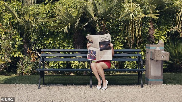 Girl in the Garden: The clip begins with Zoe sitting on a park bench in a red dress and cute kitten heels with a bow on top as she reads the newspaper