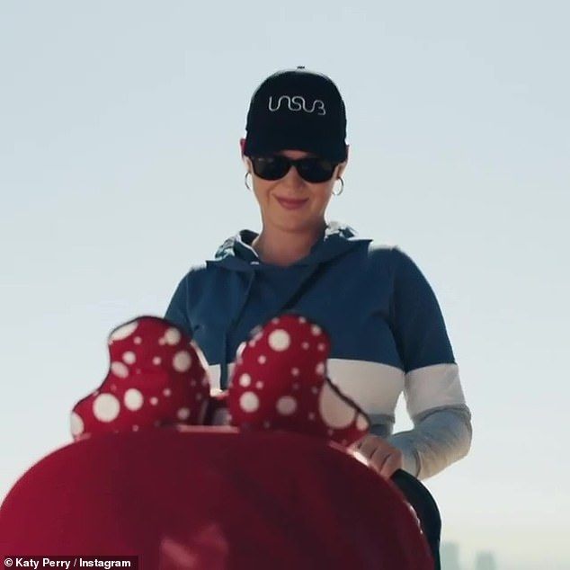 Good mom: Katie wears a hat with sunglasses and hoop earrings as she pushes the stroller red