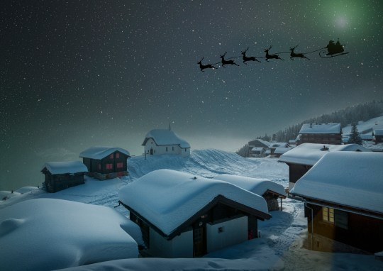 Santa's sleigh in a starry sky over a village in the snow