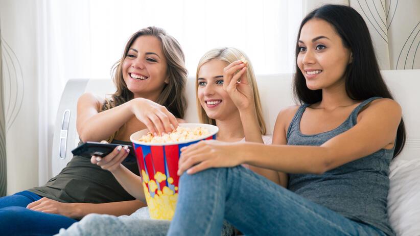 Trzy dziewczyny siedzą na kanapie i z uśmiechem na twarzy oglądaj film